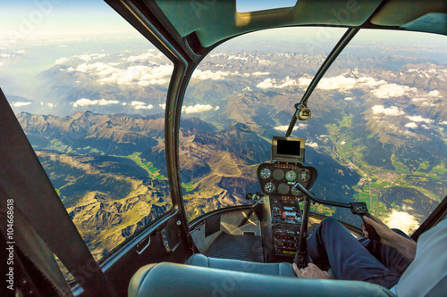 Photo Stands Helicopter Helicopter cockpit flying on mountain landscape and cloudy sky, with pilot arm driving in cabin. Spectacular aerial view of Alps mountain chain.
