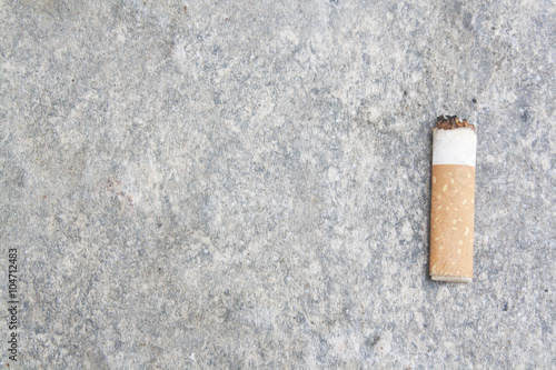 Fotografija  Cigarette butt on cement ground