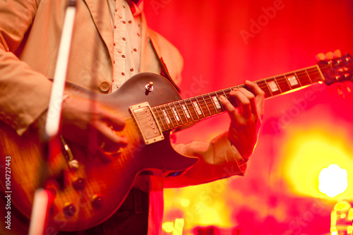 Fotografering  Musician plays on guitar in grey jacket