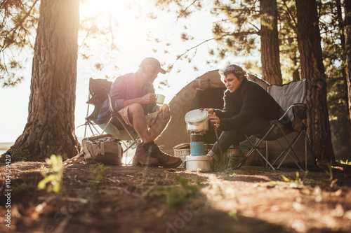 Poster Camping Couple cooking food outdoors on a camping trip