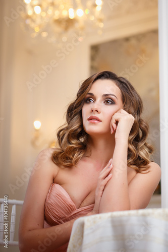 Close-up portrait of beautiful young woman in pretty beige evening dress sitting Canvas Print