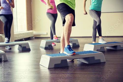 Fotomural group of people flexing legs on step platforms