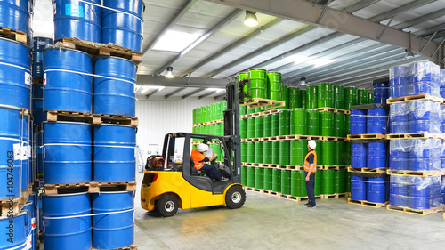 Obraz na płótnie Pracownicy logistyki // Ładowanie niebezpiecznych towarów / chemikaliów w hali przemysłowej za pomocą wózka widłowego
