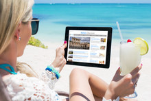 Woman Reading News On Tablet While Relaxing On The Beach. All Website Contents Are Made Up.