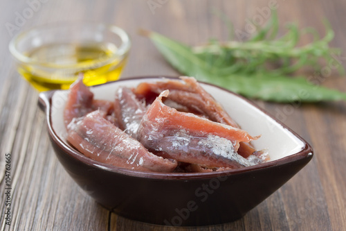 Photo anchovies in dish with oil and herbs on brown wooden background