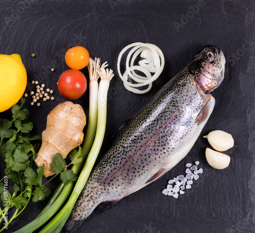 Photo  Fresh whole raw fish and herbs displayed on natural slate