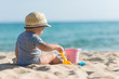 Cute baby on tropical beach playing toys