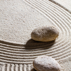 Fototapeta na wymiar zen sand still-life - two stones showing the direction for concept of evolution with care and peace, closeup