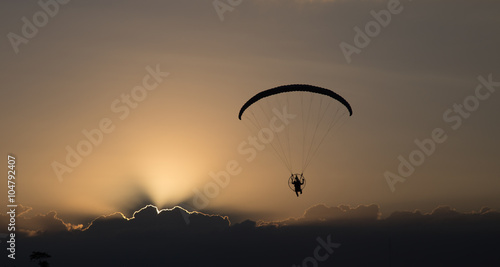 In de dag Luchtsport Silhouette paramotor / paraglider flying on sky.