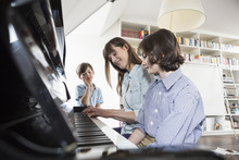 Germany, Saxony, Mother And Daughter Playing Piano While Brother Listening