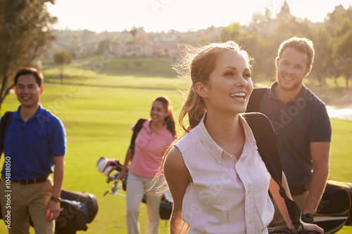 Tuinposter Golf Group Of Golfers Walking Along Fairway Carrying Golf Bags