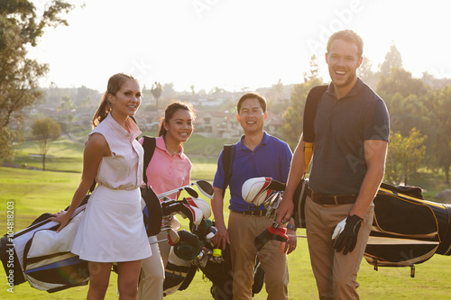 Deurstickers Golf Group Of Golfers Walking Along Fairway Carrying Golf Bags