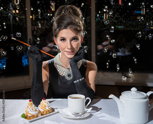 Photo  Smoking Woman in a restaurant, drink tea and eat cake