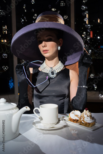 Woman in hat and glasses, much like the famous actress, Cake eating and drinking tea Canvas Print