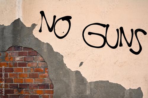 Valokuva  Handwritten graffiti No Guns sprayed on the wall, anarchist aesthetics