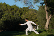 White Dressed Man Practicing Tai-Chi In The Park