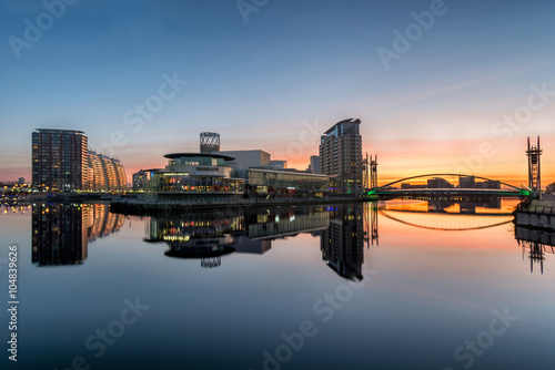 Orange sunrise at Salford Quays with blue sky and clear reflections in canal Canvas Print