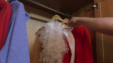 Man Opening The Closet Door And Pulling Out Santa Claus Suit Costume