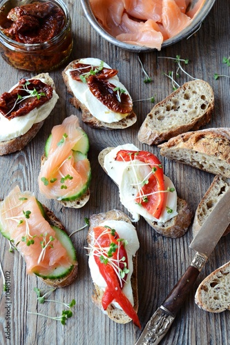 In de dag Voorgerecht Appetizers. Toasts with salmon, dried tomatoes and sweet peppers