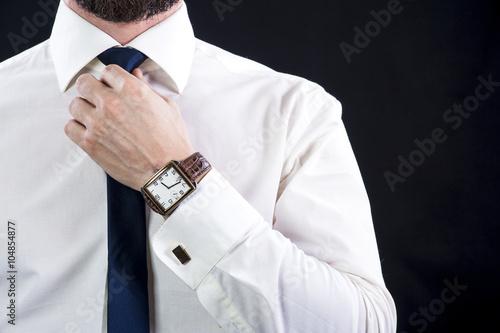 Fotografía  Elegant bearded man in white shirt tying up his necktie.