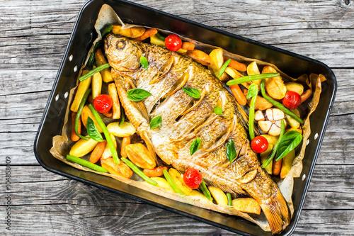 Plakat cała ryba pieczona w naczyniu do pieczenia, widok z góry