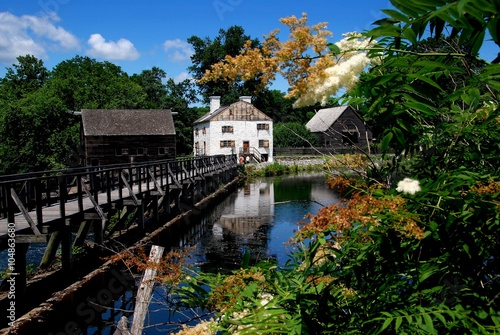 Fotografie, Obraz  Sleepy Hollow, NY - July 9, 2009:  Wooden mill pond bridge, grist mill, manor house, and old Dutch barn at historic c