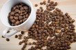 coffee beans in cup. Coffee cup and coffee beans on wooden background. coffee with cinnamon, coffee with additives