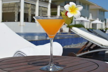 Orange Passion Fruit Alcoholic Cocktail Drink In A Tall Glass, Yellow White Flower, White Sun Loungers, A Building, Blue Sky