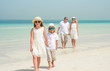 Adorable little girl with family walking along a tropical beach