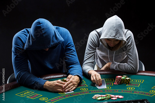 Two professional poker players sitting at a table плакат