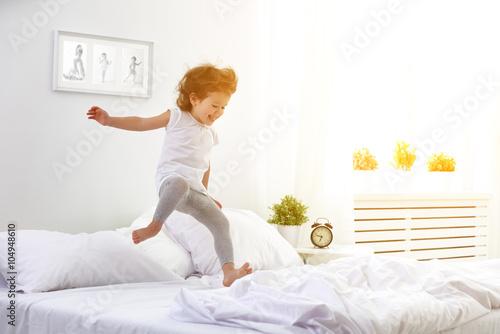 Cuadros en Lienzo Niña feliz niño salta y juega la cama