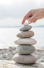 Close-up Of Woman's Hand Balancing A Stack Of Stones On A Sunny Beach