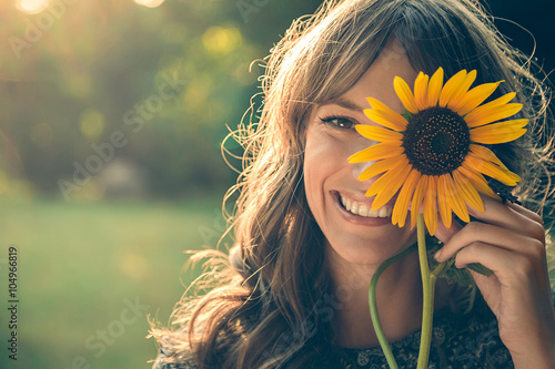 In de dag Zonnebloem Girl in park covering face with sunflower