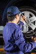 Mechanic Filling Car Tire At Garage