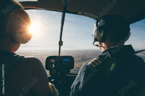 Valokuvatapetti Two pilots in a helicopter while flying on a sunny day