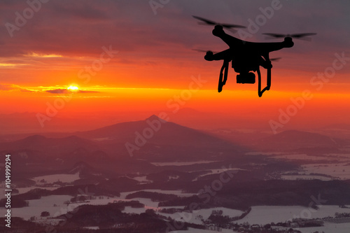 Drone silhouette flying in sunset landscape
