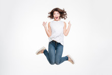 Full Length Portrait Of A Cheerful Cute Woman Jumping