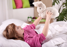 Cute Little Blonde Girl Lying In Bed Playing With Plush Bunny