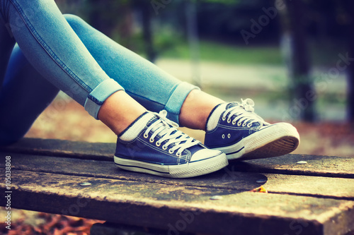 Fotografía  Young woman in jeans and blue sneakers on a bench in the park