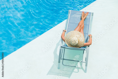 Tableau sur Toile woman enjoying on sunbed at swimming pool