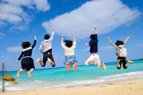 ビーチでジャンプをする若者