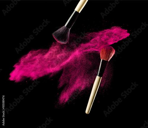 Obraz na plátne Make-up brush with pink powder explosion on black background