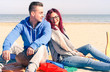 Young couple on the beach sitting back to back in a sunny spring day - Love and tenderness sun and nature concept with soft vintage filter - Cheerful friends relaxing on the shore in the early summer