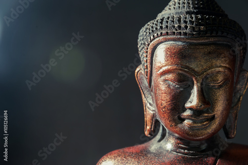 Tuinposter Boeddha Wooden bronze buddha on black blurred background close up