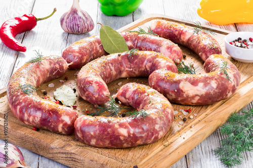 plakat raw sausages prepared for grill with chilli pepper, garlic, close-up