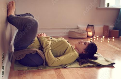 Attractive mixed race woman doing restorative yoga Fotobehang