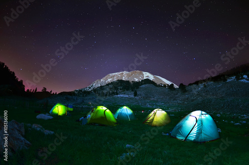 Montage in der Fensternische Camping Illuminated yellow camping tent under stars at night