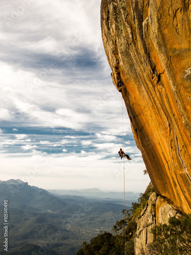 Spoed Fotobehang Alpinisme Abseiling a negative yellow rock wall with mountains on backgrou