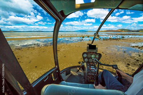 Tuinposter Helicopter Elicopter cockpit flying in a blue cloudy sky, with pilot arm in driving cabin. Tasman Peninsula, Australia