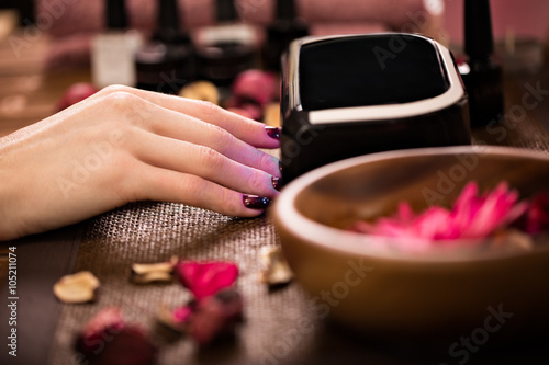 Photographie  Closeup finger nail care by manicure specialist in beauty salon.